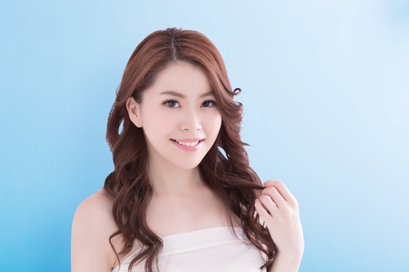 Beauty woman with charming smile to you with health skin, teeth and hair isolated on blue background, asian beauty