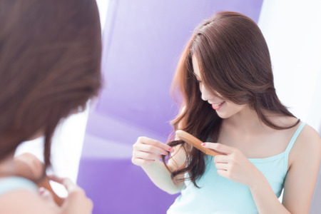 comb hair: young woman is combing hair in bathroom at home
