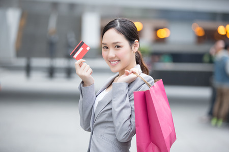 go to the shopping: businesswoman take a credit card and bag go shopping in hon kong, asian Stock Photo
