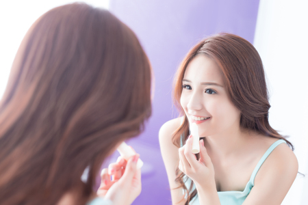 beatification: a young woman is  painting  lip balm in bathroom at home