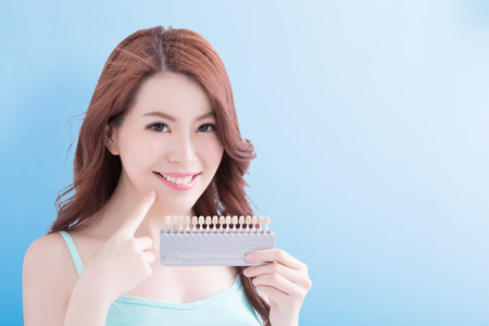 Beautiful young woman with health teeth and hold teeth whitening tool. Isolated over blue background, asian beauty