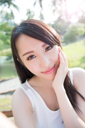 hands free phone: young woman selfie and smile to you with nature green background