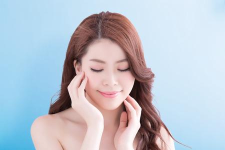 transparente: Mujer de la belleza con una sonrisa encantadora a usted con la salud de piel y el pelo aislado en el fondo azul, belleza asiática