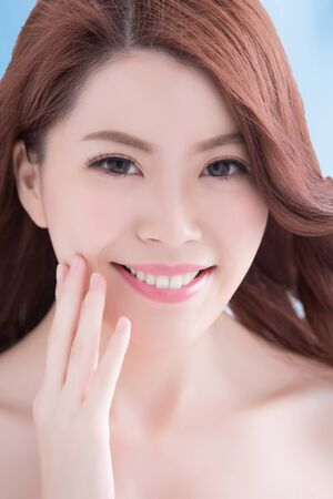 beautiful teeth: Beautiful young woman with health teeth and charming smile. Isolated over blue background, asian beauty