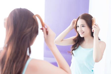 mujer joven está peinando el pelo en el baño en el hogar