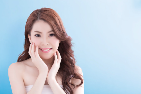 beauty skin: Beauty woman with charming smile to you with health skin, teeth and hair isolated on blue background, asian beauty