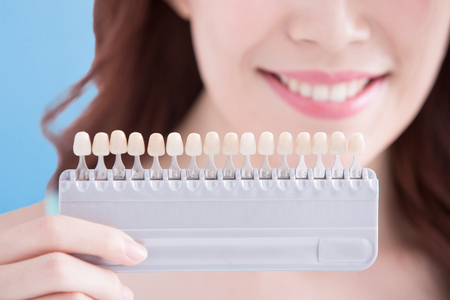 dientes: Hermosa mujer joven con dientes de salud y mantenga pulsado para blanquear los dientes herramienta. Aislado sobre fondo azul, belleza asiática