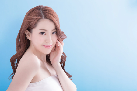 elegance: Beauty woman with charming smile to you with isolated blue background, asian