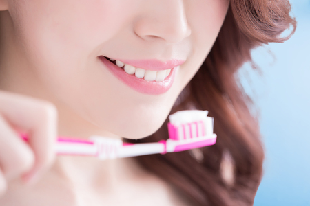 a tooth are beautiful: Beautiful young woman with health teeth and charming smile.holding the tooth brush, Isolated over blue background, asian beauty Stock Photo