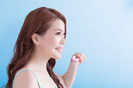 view woman: Beautiful young woman with health teeth and charming smile.holding the tooth brush, Isolated over blue background, asian beauty Stock Photo
