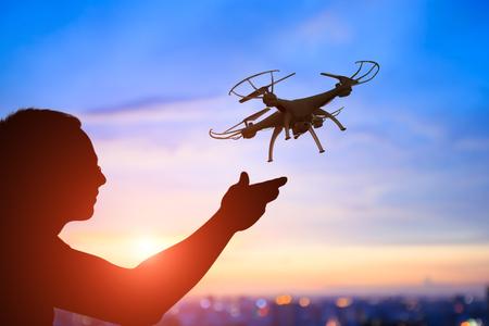 iluminado a contraluz: silueta de hombre jugar drone en la puesta de sol, asiático