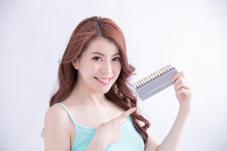Schöne junge Frau mit der Gesundheit Zähne und halten Sie Zahnweiß-Werkzeug. Isolierte über weißem Hintergrund, asiatische Schönheit