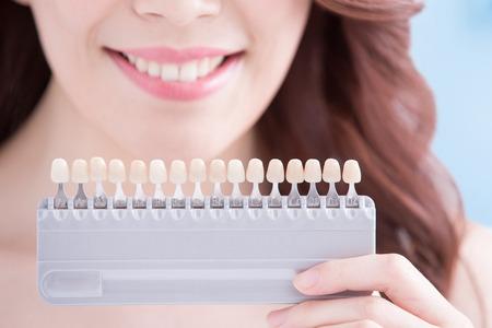Belle jeune femme avec des dents de santé et maintenir les dents outil de blanchiment. Isolé sur fond bleu, la beauté asiatique Banque d'images - 61229601