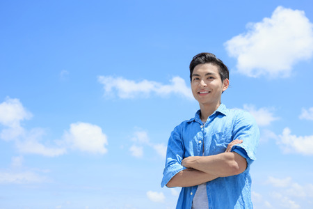 man smile happily to you with blue sky, asian