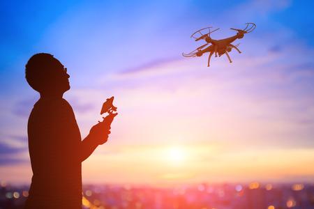 sylwetka człowieka zabaw drona w zachodzie słońca, asian