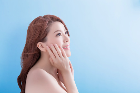 blue face: beauty skin care woman face and look some where with isolated blue background, asian