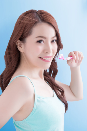 Beautiful young woman with health teeth and charming smile.holding the tooth brush, Isolated over blue background, asian beauty Stock Photo