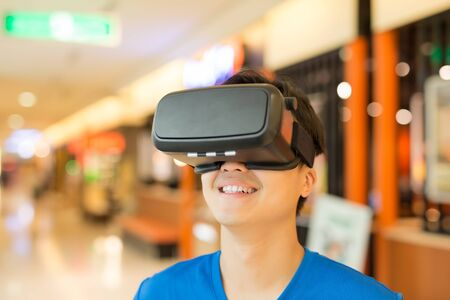 virtual reality simulator: man wear virtual reality headset happily, asian
