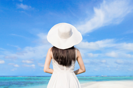 woman back view: young woman wear dress and relax look beach and sea