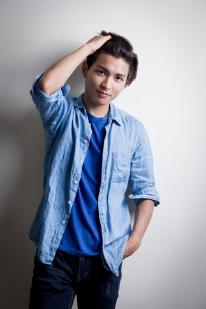 handsome man wear denim shirt and look serious,isolated white background,asian
