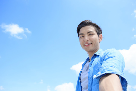 man smile happily and take a selfie with blue sky, asian Stock Photo