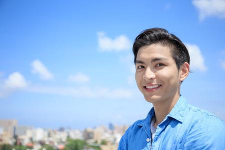 hombre sonríe feliz a usted con el cielo azul, asiático