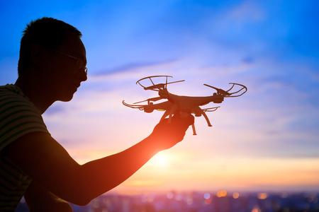 iluminado a contraluz: silueta de hombre juego avión no tripulado en la puesta del sol, asiático Foto de archivo