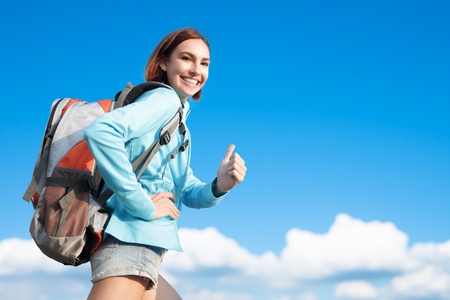 travel woman: happy woman mountain hiker go to travel and show thumb up with blue sky and white clouds, caucasian Stock Photo