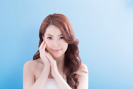 Beauty Frau mit einem charmanten Lächeln Sie mit blauem Hintergrund isoliert, asiatisch