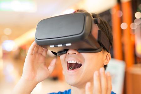 hombre llevar casco de realidad virtual de feliz, asiático Foto de archivo