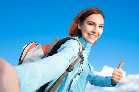 hands free phone: happy woman mountain hiker show thumb up and take a selfie with blue sky and white clouds, caucasian