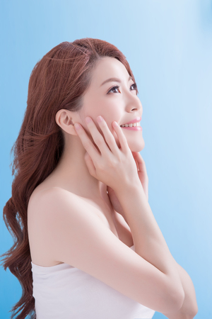 touch: beauty skin care woman face and look some where with isolated blue background, asian