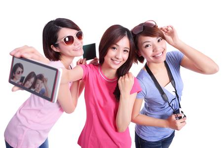 Adolescentes felices mujer que toma imágenes por sí mismos aislados sobre fondo blanco, asiático