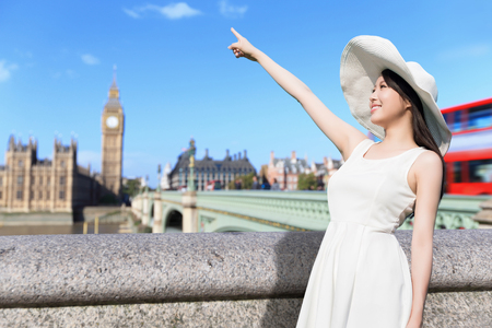 young woman wear dress and smile with Big Ben in london, UK