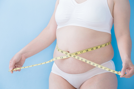 slim women: Fat overweight woman take waist ruler amount with blue background, asian Stock Photo