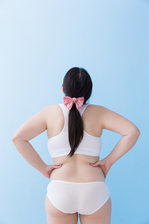 Back view of Fat overweight woman body with blue background, asian