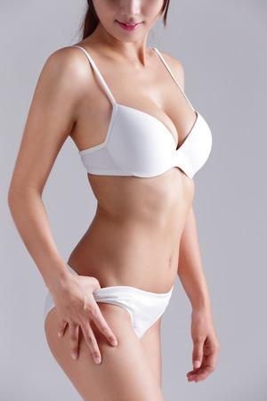 Schöne schlanke Körper der Frau auf grauem Hintergrund isoliert Standard-Bild