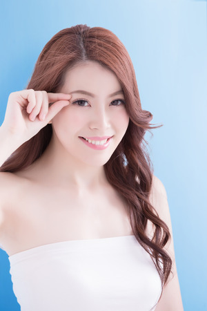 chinese lady: Woman face and eye care and she touch eye with hands, asian beauty. Isolated over blue background, asian beauty