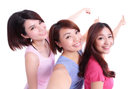 asian group: Happy teenagers woman taking pictures and show something by themselves isolated on white background, asian Stock Photo