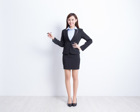 business woman writing something on white wall background, great for your design or text, asian