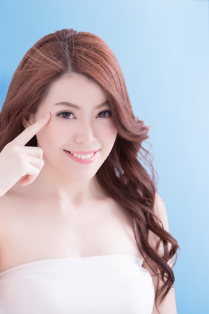 Woman face and eye care and she touch eye with hands, asian beauty. Isolated over blue background, asian beauty