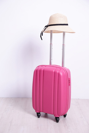 luggage travel: pink luggage case with white wall background
