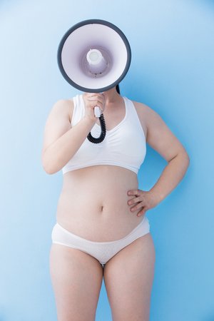Fat overweight woman take microphone with blue background, asian