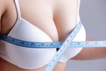 senos: Mujer joven que controla su medición de pecho aislado sobre fondo gris, belleza asiática