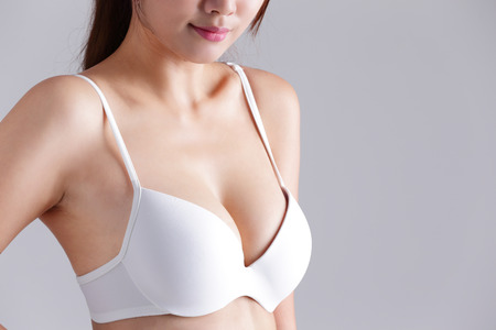 beauty breast: Closeup view of a young woman body chest breast with bra isolated on gray background, asian beauty