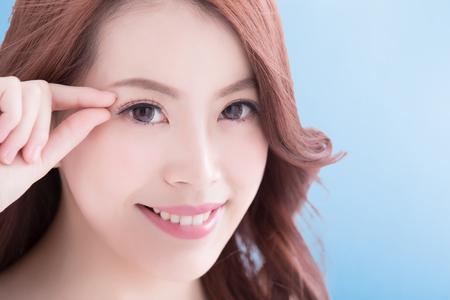 Frau Gesicht und Augenpflege und sie berühren Auge mit Händen, asiatische Schönheit. Isoliert über blauem Hintergrund, asiatische Schönheit