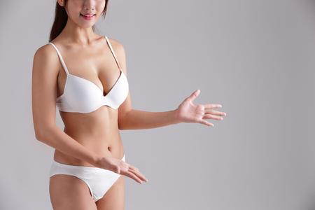 ropa interior: cuerpo delgado hermoso de la mujer y ella mostrar el espacio copia algo aislado en el fondo gris
