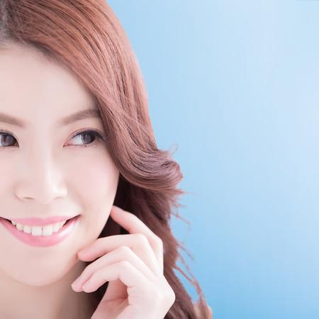 Schoonheid vrouw met charmante glimlach aan u met gezondheid van de huid, tanden en haren geïsoleerd op een blauwe achtergrond, Aziatische schoonheid