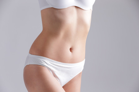 Beautiful slim woman body and sexy belly isolated on gray background Stock Photo