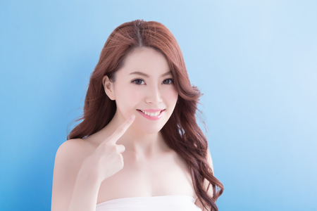 Beauty woman with charming smile and show her teeth isolated over blue background, asian beauty